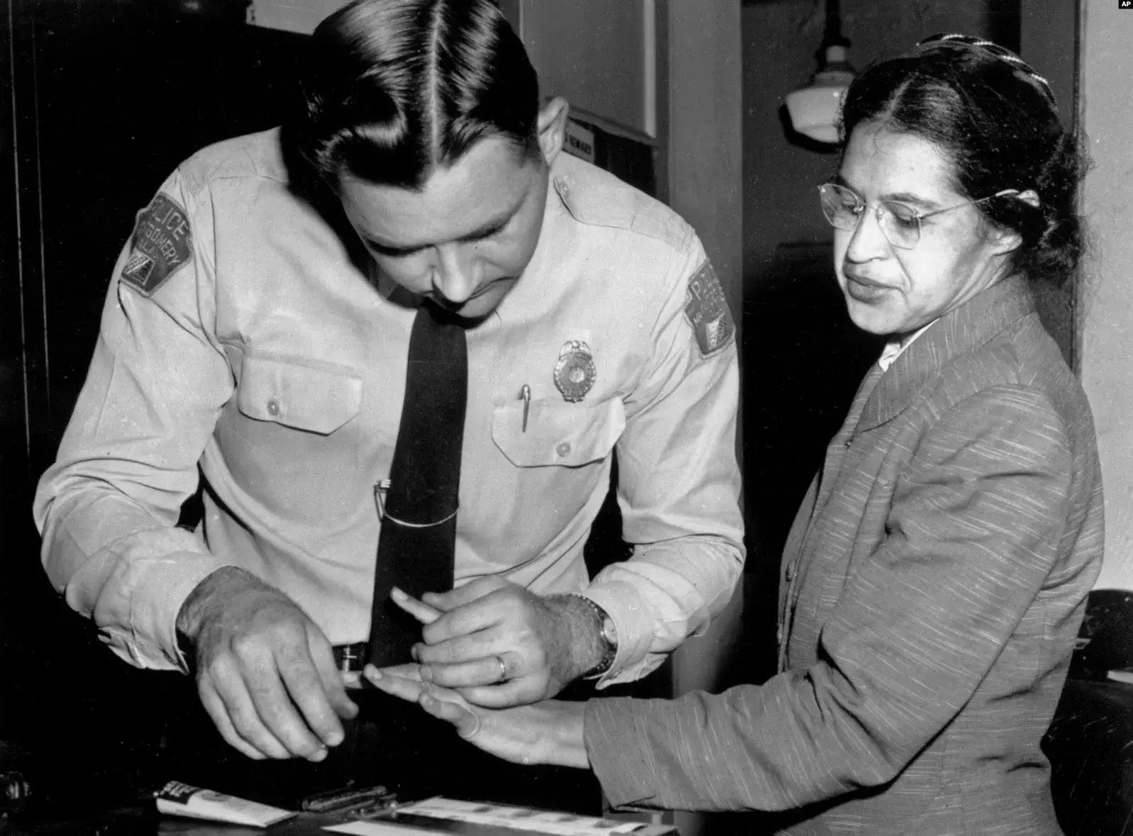 Dalam foto pada 22 Februari 1956 ini, Rosa Parks diambil sidik jarinya oleh polisi Letnan D.H. Lackey di Montgomery, Alabama, setelah menolak menyerahkan kursinya di bus untuk penumpang kulit putih pada 1 Desember 1955