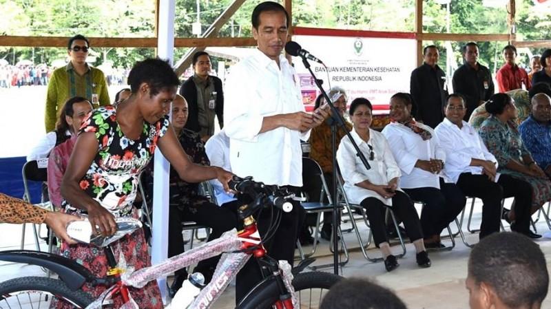 Presiden Jokowi memberikan sepeda saat berdialog dengan warga Papua