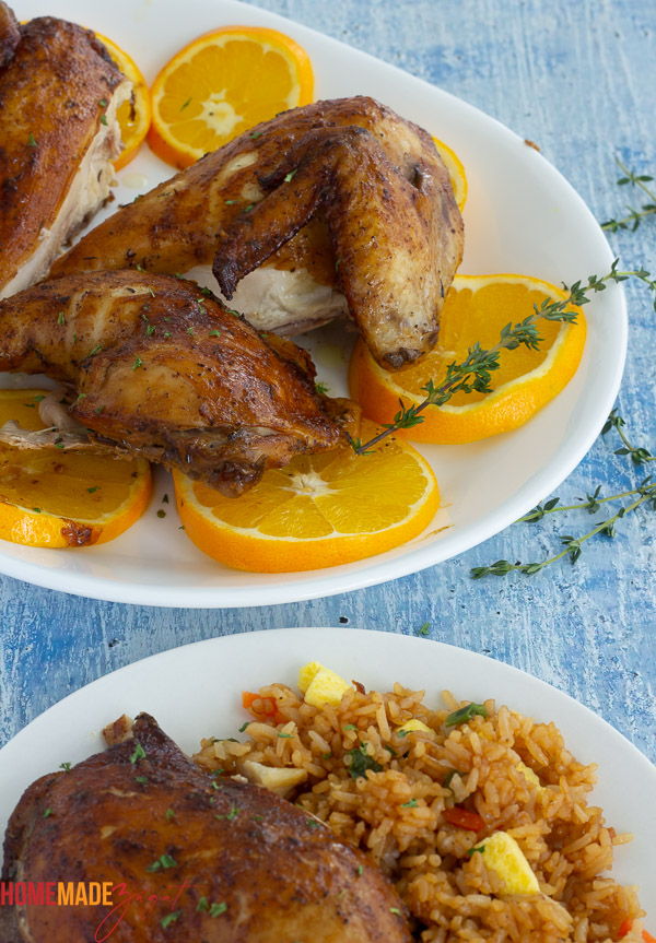 Close up of the roasted chicken, cut into pieces to be served on a plate with orange slices.