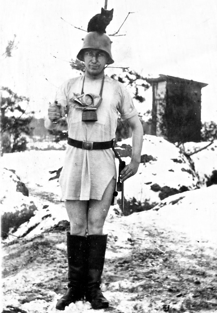 Snapshot WWII German soldier standing in the snow in his undershirt, boots and helmet with a cat on his head. Situation Normal, and other stories of The Better Defense. marchmatron.com
