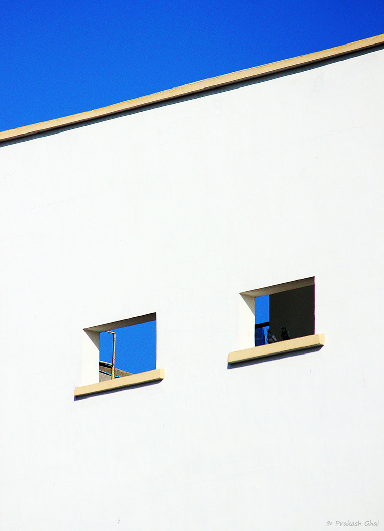 A minimalist photo of Two small rectangles on the walls of a high-rise building