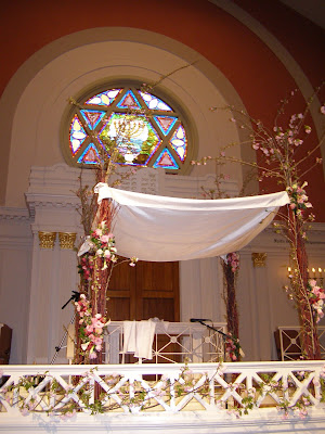 ID: a Chuppah set up at the front of a synogogue. A stained glass Magen David looks over the Chuppah and the unpictured congregation.