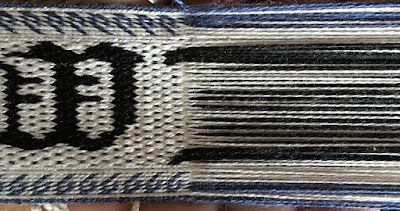 A photo of a section of tablet woven band with the weft removed and the twist between the tablets and the band removed