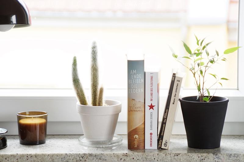 Fensterbank kreativ dekorieren mit Nachttischleuchte, Pflanzen, Büchern und Duftkerze im skandinavischen Stil