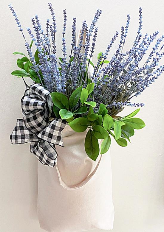muslin tote filled with flowers hanging on wall
