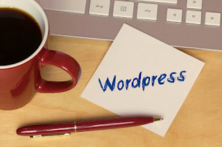 taza de café, un bli y ordenador acompañando a un cartel que dice WordPress