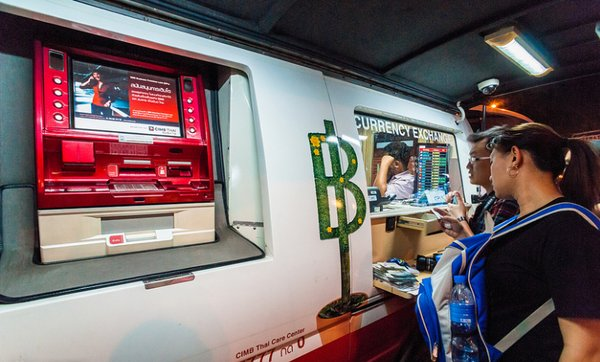 Туристы обменивают деньги в автобанке