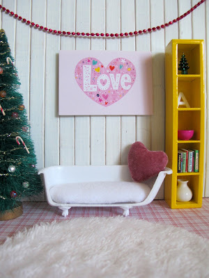 Modern miniature dolls house scene with a christmas tree, bathtub sofa and a 'love' picture on the wall and matching heart-shaped cushion on the sofa.
