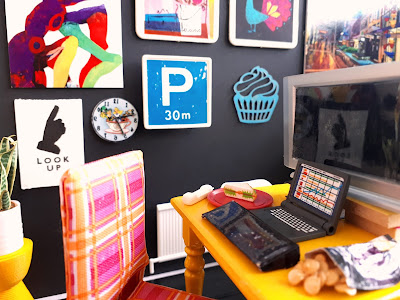 One-twelfth scale modern miniature scene of a yellow dining table set up as a home office, with monitor, laptop and keyboard, cordless phone, and a sandwich and bag of chips.