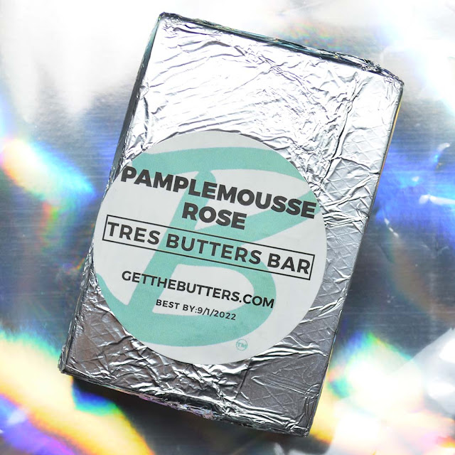 soap bar tightly wrapped in foil against holographic background