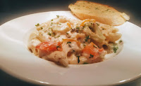 Pasta in white sauce with a garlic bread