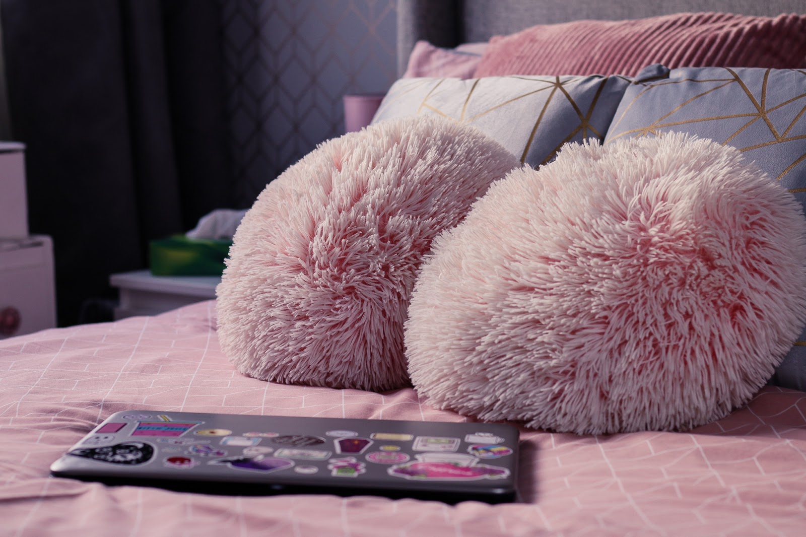 Close up photo of a silver HP laptop on a double bed with pink bedding and two fluffy pink pillows