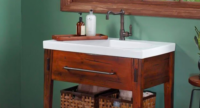 A rustic wood vanity by Ronbow stands out in this sage green bathroom.