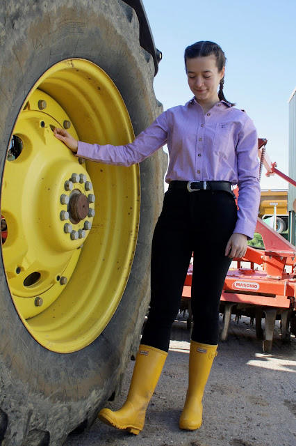 Abbey wearing a lilac shirt, jeans and yellow wellies stands next to a yellow tractor tyre