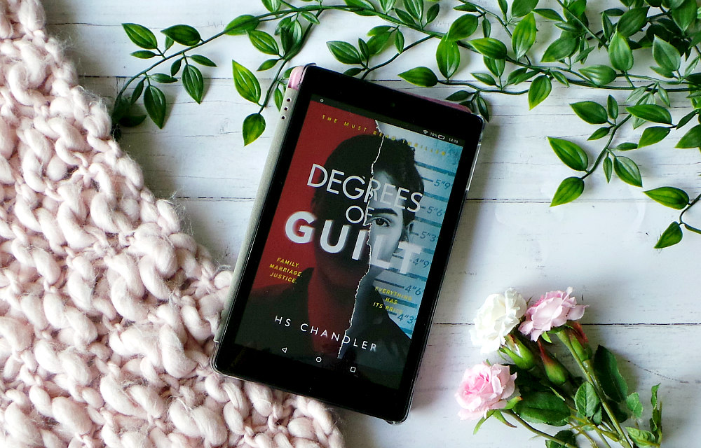 Kindle fire shows the cover of Degrees of Guilt next to a pink chunky knit blanket, leaves and roses. The cover shows a photo of a woman torn down the middle. The left side is red and the right side is a mug shot