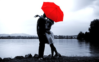 girl-hugs-and-kisses-her-love-boy-behind-umbrella-covering-near-lake-image.jpg