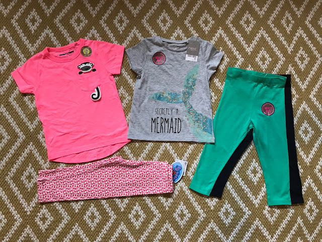 "A selection of Next clothes on a rug: a pink ""boys"" t-shirt with a monkey on the breast pocket, a pair of leggings with a white background and lots of little peppa pigs, a grey t-shirt with a fishes tail and text saying ""secretly a mermaid"" and a two pack of leggings (green and navy)"