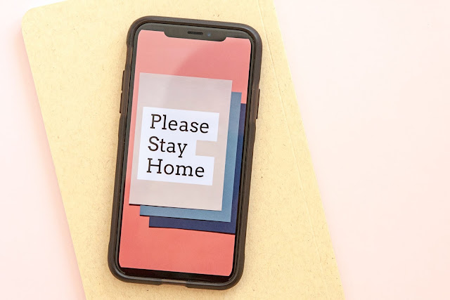 "smartphone displaying the text ""please stay home"" during lockdown"