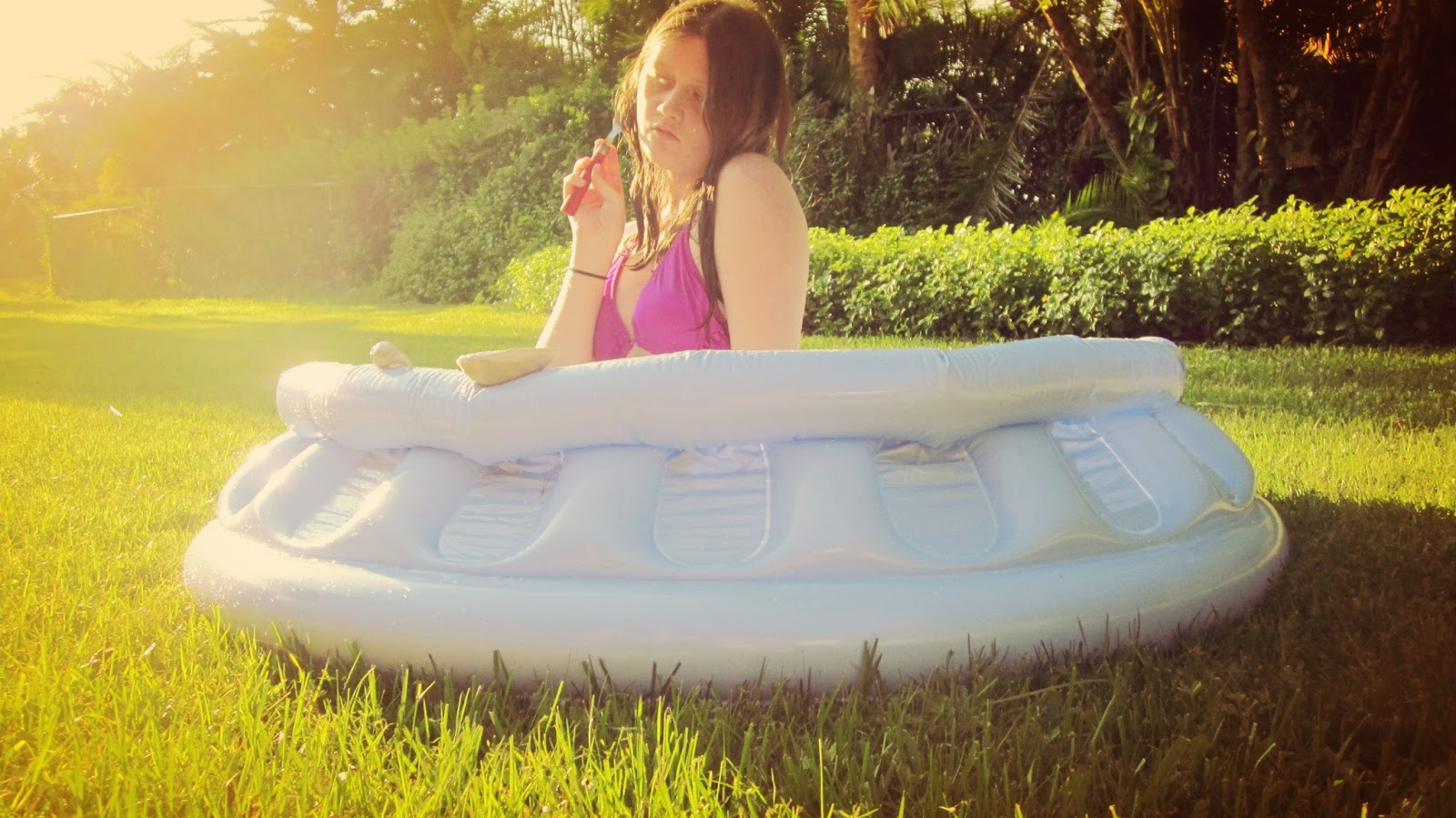 A young girl in a blue inflatable kiddie pool in the hot Florida sun in the summertime