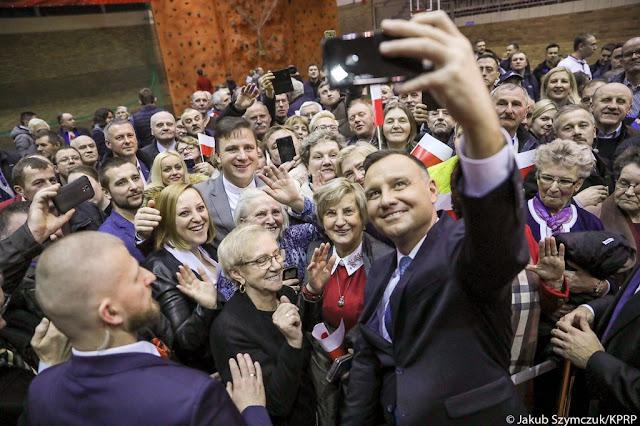 Widok Andrzej Dudy podczas robienia sobie selfie z mieszkańcami Kolna