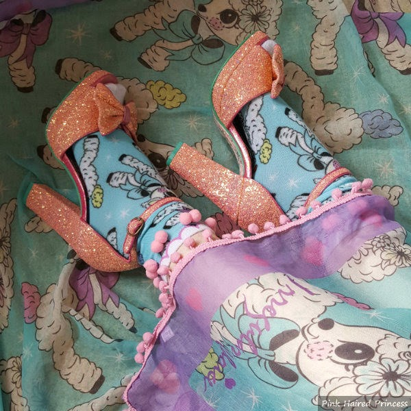 lamb print scarf draped across leg wearing lamb socks and glitter shoes
