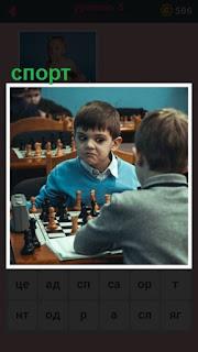 за столом двое мальчиков играют в шахматы, спортивная игра