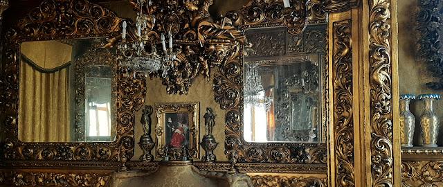 Sala com espelhos e revestida com madeira talhada