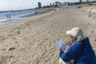 スケッチの様子 (家内の撮影)砂浜には家族連れやカップル、海ではウィンドサーフィン。