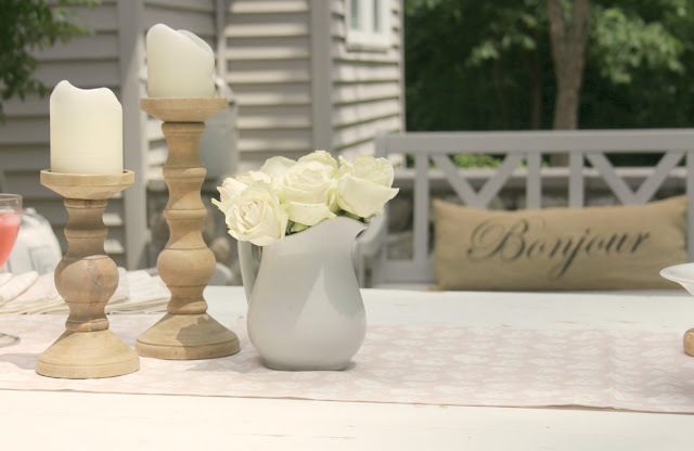 Blush pink runner with wood candlesticks on farm table in courtyard - Hello Lovely Studio