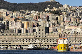 Tall apartment buildings cling to the hillside rising from Genoa's port and shipyards