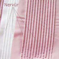 Pembe ve beyaz renkli parlak bir kumaşta dikiş ile yapılmış nervür çizgileri
