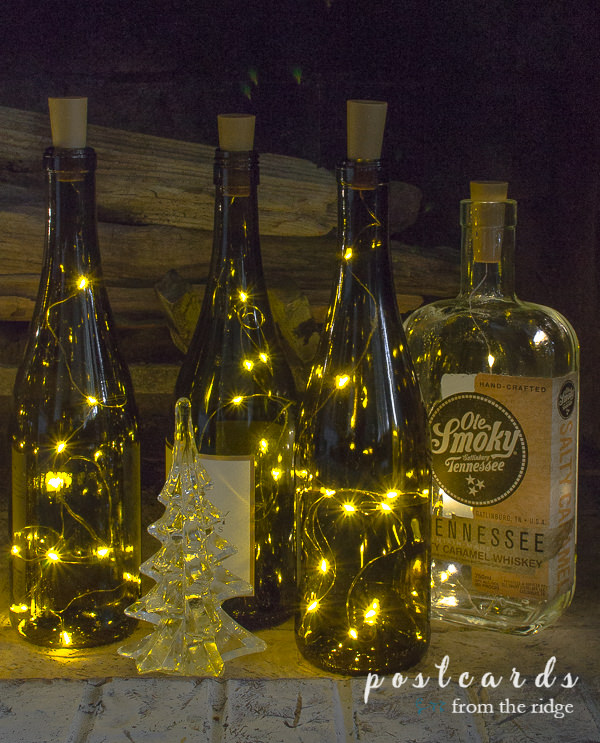 glass Christmas tree and bottles with lights
