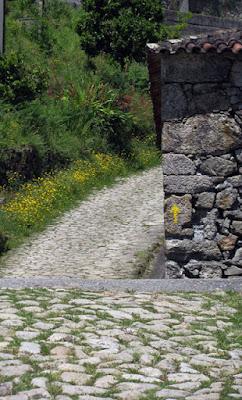 Caminho e parede de pedras com seta amarela