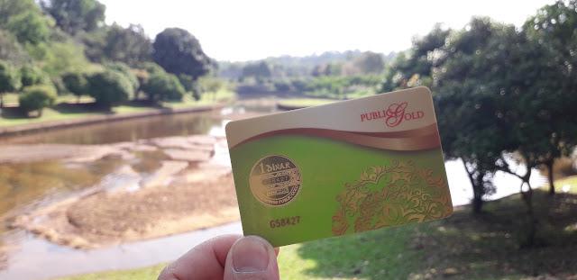 1 dinar public gold berlatarbelakang taman tasik