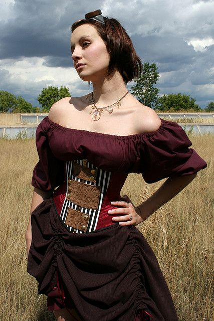 Girl wearing gypsy or pirate style steampunk clothing. Red/wine/maroon off the shoulder peasant blouse, black and white striped corset, brown pinstripe bustle skirt, necklace, goggles. Steampunk fashion for women.