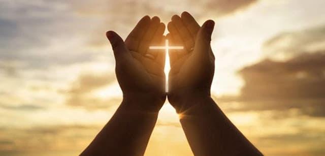 A imagem mostra mãos em formato de oração com uma cruz iluminada pelo sol ao fundo