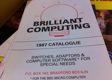 "An outline of a red bulb, with black text reading, ""Brilliant Computing 1987 Catalogue. Switches, adaptors and computer software for the BBC Micro computer for special needs. PO Box 142, Bradford, BD3 0JN."