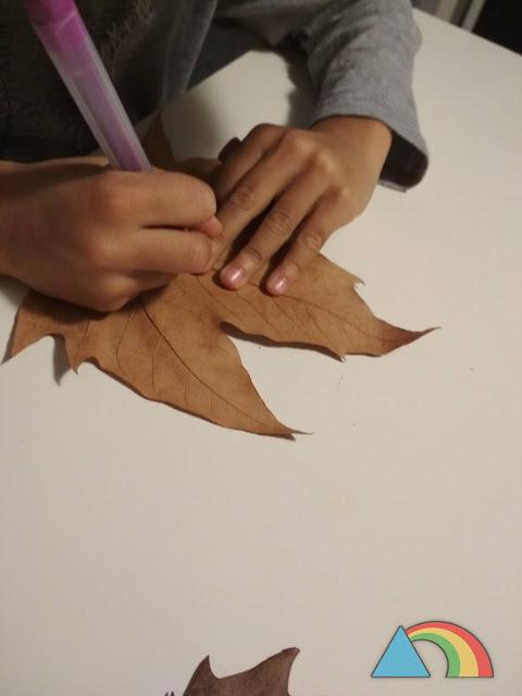 Niño decorando hoja seca con rotuladores