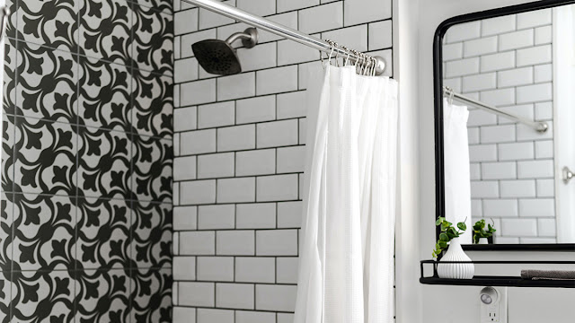 Shower wall with white subway tile an dark grout.