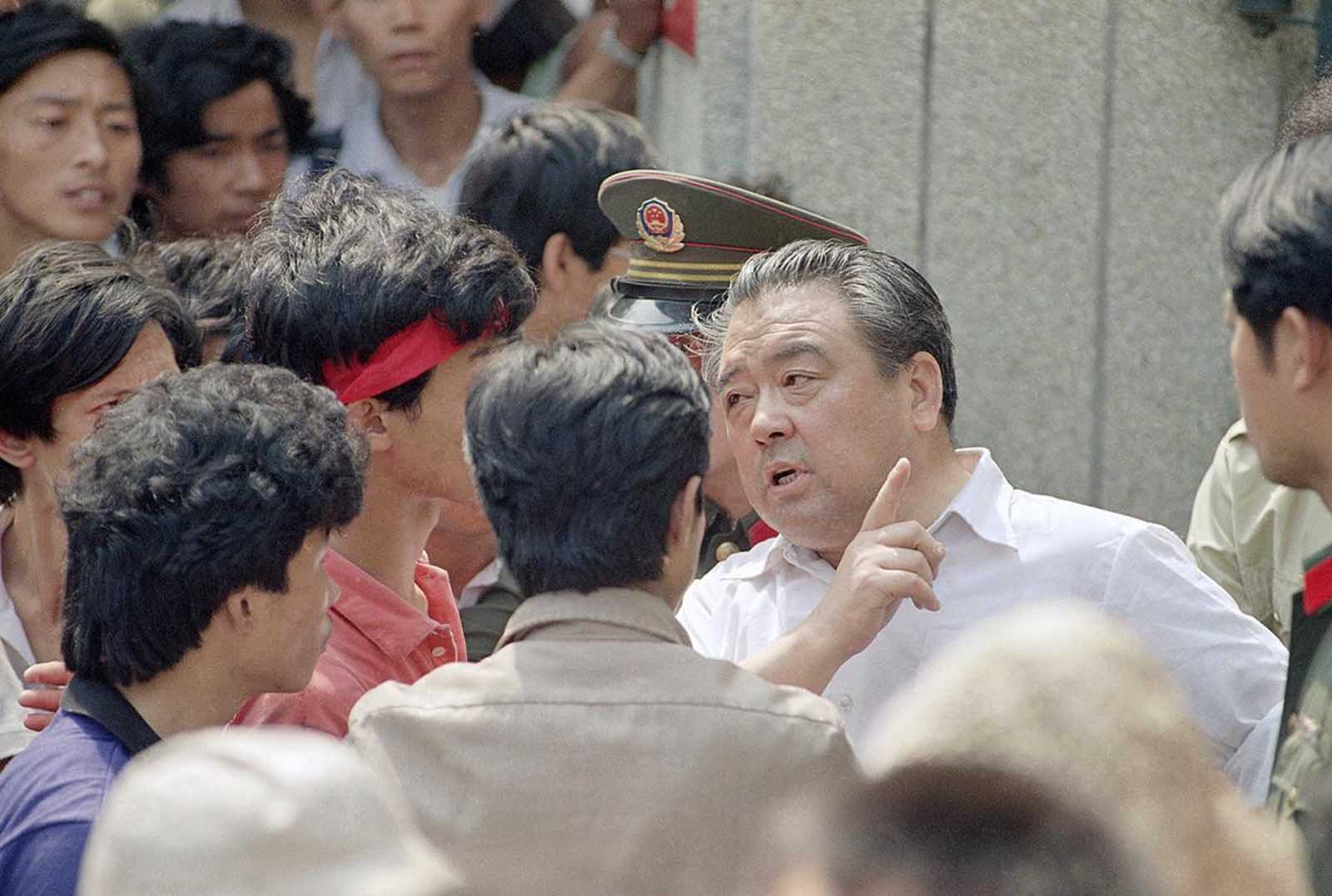 A plainclothes policeman tells students protesting in front of Beijing police headquarters that their activities violate martial law, on May 30, 1989, in Beijing.