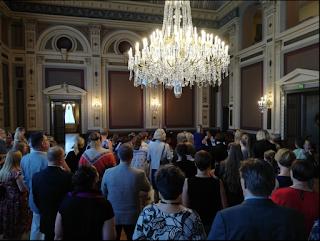 Raatihuoneen iso sali on täynnä vieraita, takana näkyy Ahjolan orkesterin soittajia ja katossa roikkuu valtavan kokoinen kristallikruunu.