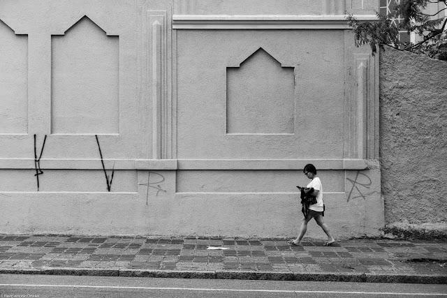 Mulher caminhando olhando para o telefone celular
