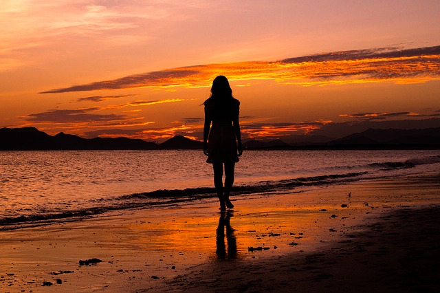 silhouette of woman on beach at sunrise or sunset, with pink-y light contrasting with shadows in scene