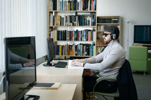 Blind man sitting at desk with computer and paper on desk.