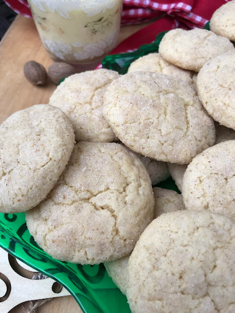 A close-up of baked eggnog snickerdoodles with nutmeg and a glass of eggnog.