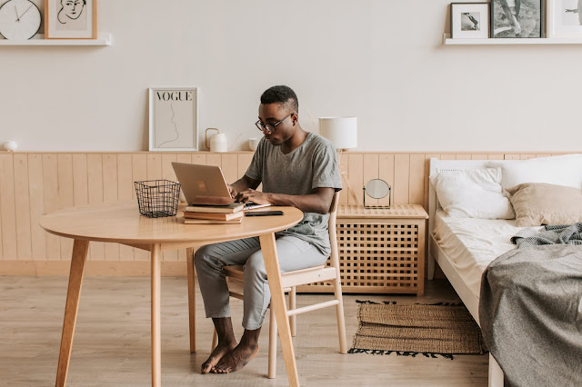 A man sat at a desk, working on a laptop, next to a bed