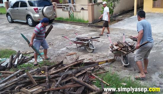 ANGKUT : Jamaah masjid sedang mengangkut kayu dan papan yang sudah tidak terpakai untuk dikumpulkan dan dibakar. Foto Asep Haryono