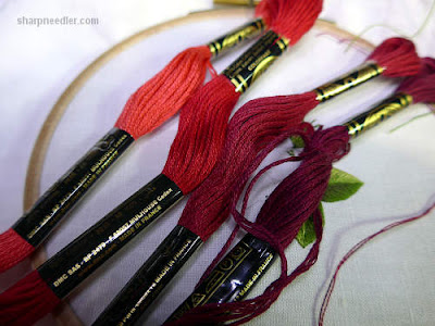 Four shades of red thread that will be used to stitch the petals on a needle painted rose