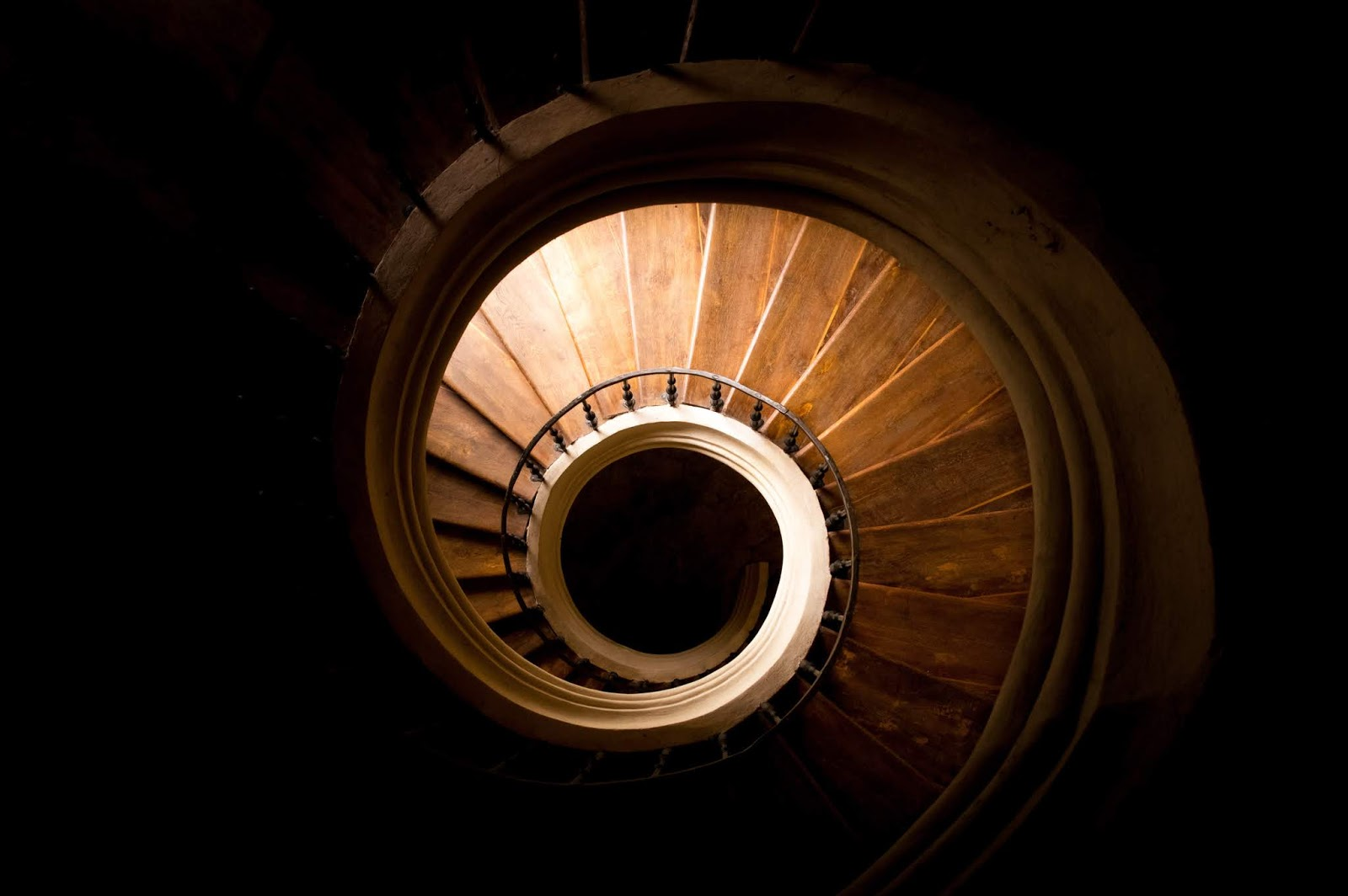 A gothic style staircase that is slowly winding down.