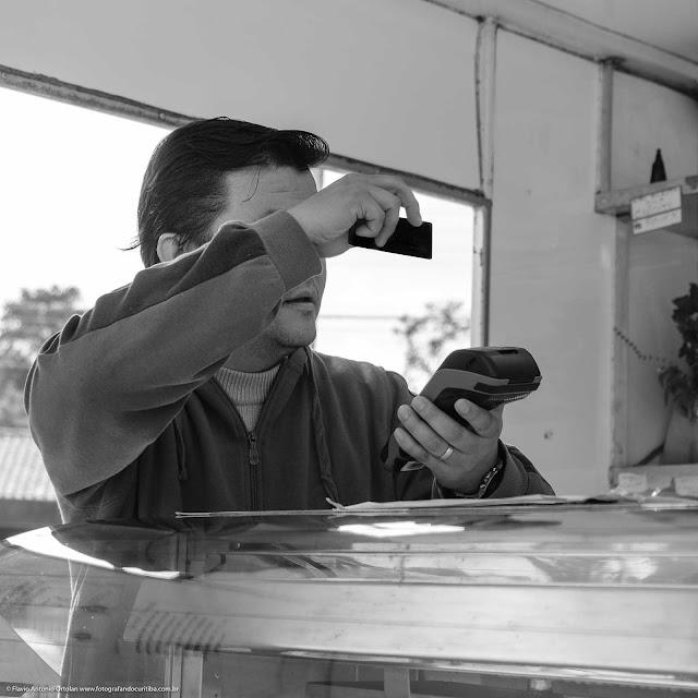 Homem passando cartão na  máquina na feira livre